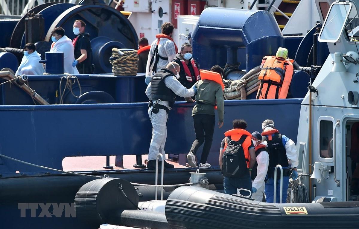 Lực lượng bảo vệ biên giới Anh đưa người di cư vượt biển từ Pháp qua Eo biển Manche, tới cảng Dover ở bờ biển đông nam nước Anh ngày 9/8 vừa qua. (Ảnh: AFP/TTXVN)