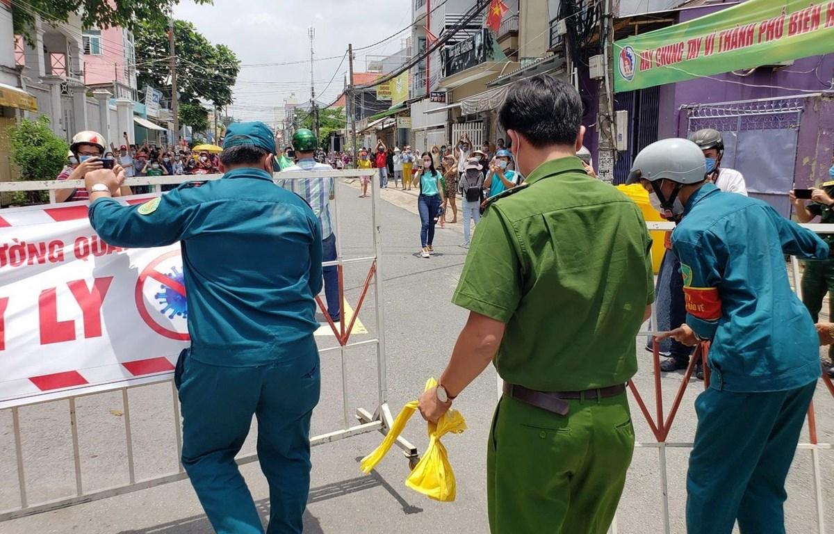 Lực lượng chức năng dỡ bỏ phong tỏa tuyến đường Hồ Văn Đại sau thời gian cách ly 14 ngày. (Ảnh: Lê Xuân/TTXVN)