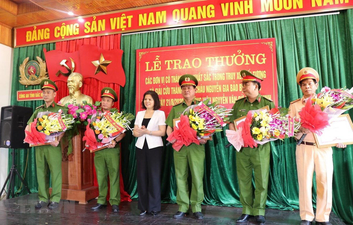 Chủ tịch UBND tỉnh Bắc Ninh Nguyễn Hương Giang trao Bằng khen, tặng hoa cho các đơn vị tham gia phá án. (Ảnh: Đinh Văn Nhiều/TTXVN)