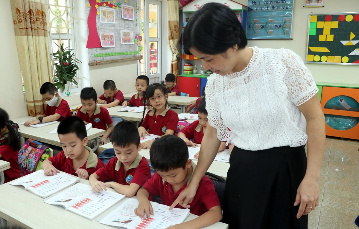 Giáo viên trường Tiểu học Chu Văn An, thành phố Nam Định, tỉnh Nam Định hướng dẫn học sinh làm bài tập. (Ảnh: Nguyễn Lành/TTXVN)