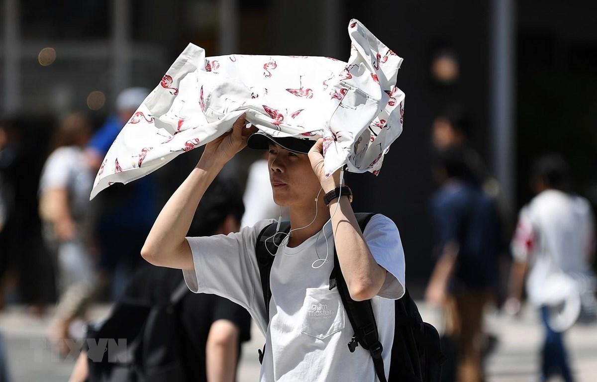 Người dân di chuyển trên đường phố dưới trời nắng nóng tại Tokyo, Nhật Bản. (Ảnh: AFP/ TTXVN)