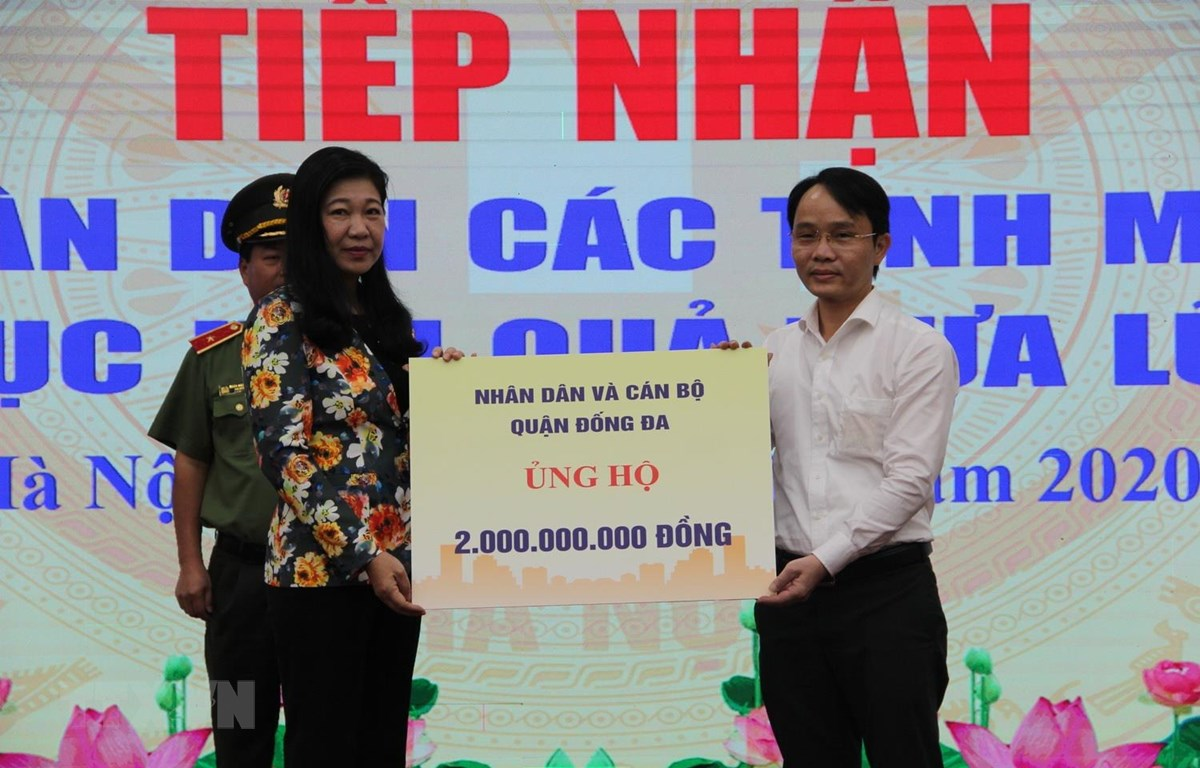 Đại diện một số cơ quan, đơn vị, doanh nghiệp trao tiền ủng hộ các tỉnh miền Trung bị ảnh hưởng bởi mưa lũ. (Ảnh: Nguyễn Thắng/TTXVN)