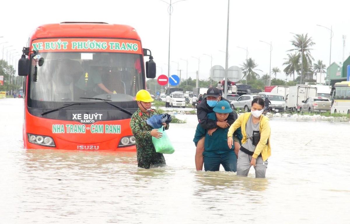 Lực lượng quân đội hỗ trợ cứu nạn người dân bị mắc kẹt trong xe buýt đến nơi an toàn. (Ảnh: Phan Sáu/Vietnam+)