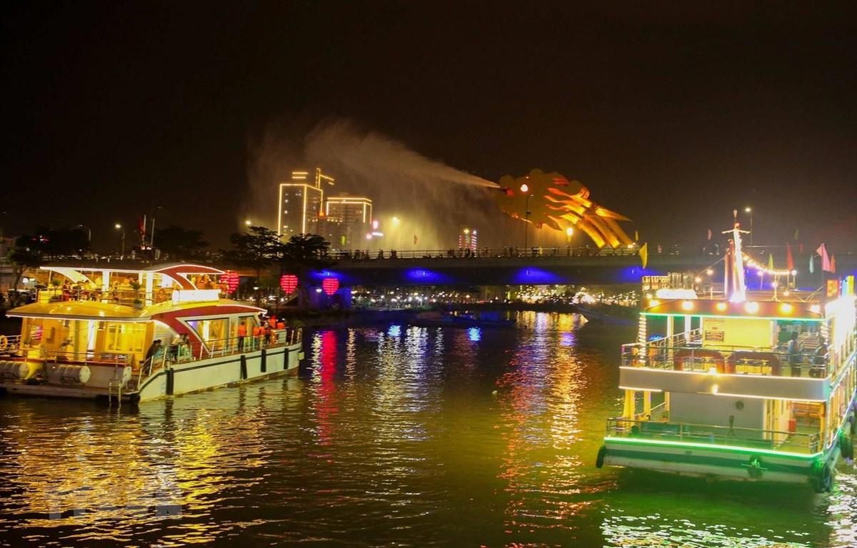 Các du thuyền đưa du khách ngắm cầu Rồng phun nước trong tour du lịch miễn phí thưởng ngoạn ngắm sông Hàn về đêm. (Ảnh: Trần Lê Lâm/TTXVN)