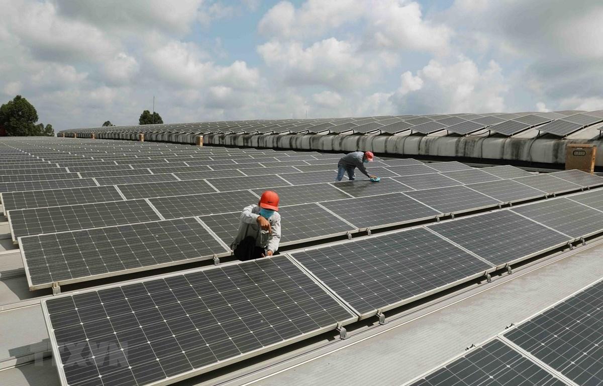 Bảo dưỡng tấm pin năng lượng Mặt Trời trên mái nhà. (Ảnh: Vũ Sinh/TTXVN)