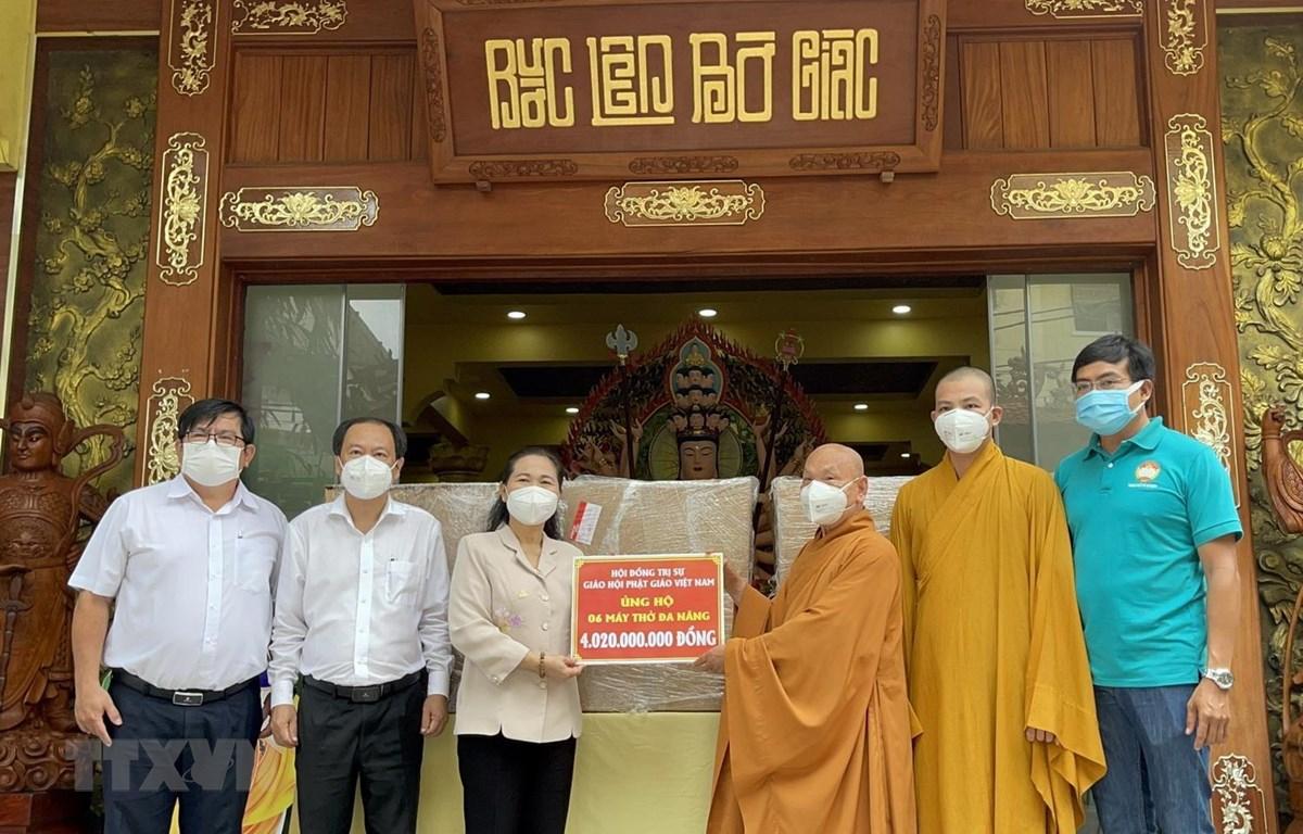 Hòa thượng Thích Thiện Nhơn trao bảng tượng trưng số máy thở đa năng cho bà Nguyễn Thị Lệ. (Ảnh: TTXVN phát)