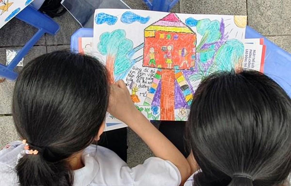 Trẻ em tham gia vào sáng tác tranh với thông điệp ngăn chặn lao động trẻ em. (Ảnh: PV/Vietnam+)