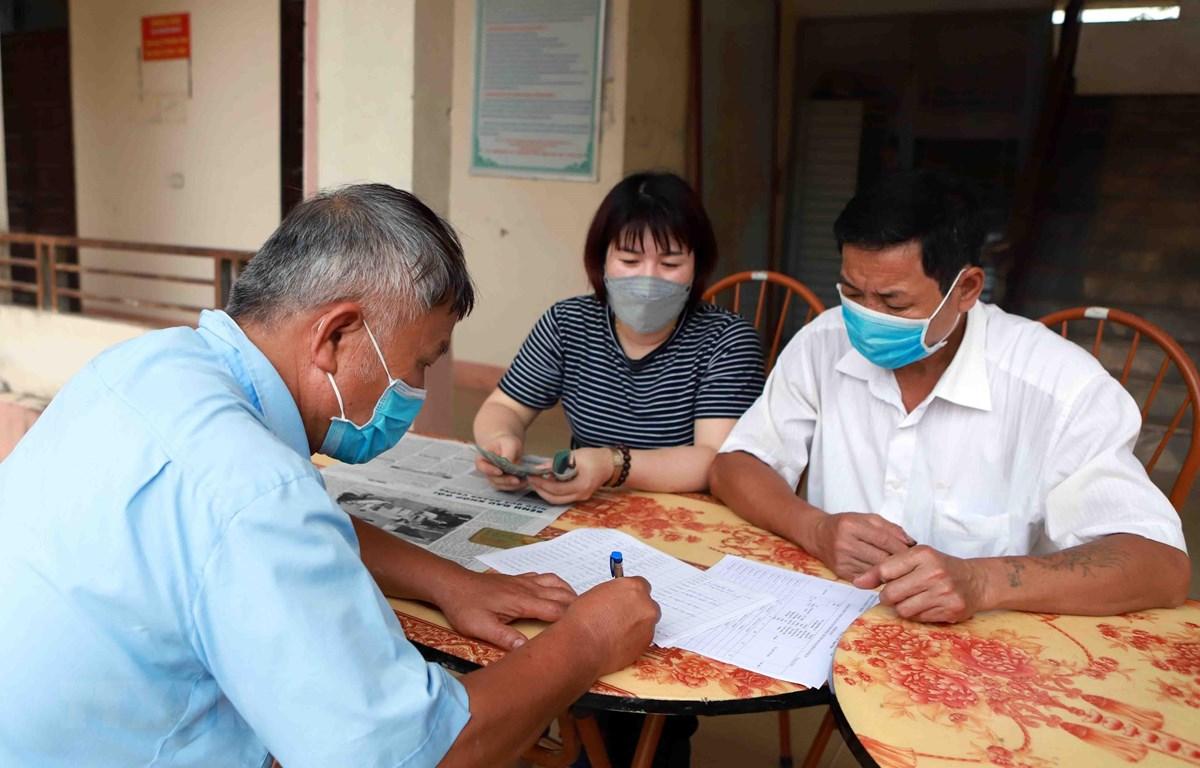 Chi trả tiền hỗ trợ cho người dân gặp khó khăn do COVID-19. (Ảnh: Hoàng Hùng/TTXVN)