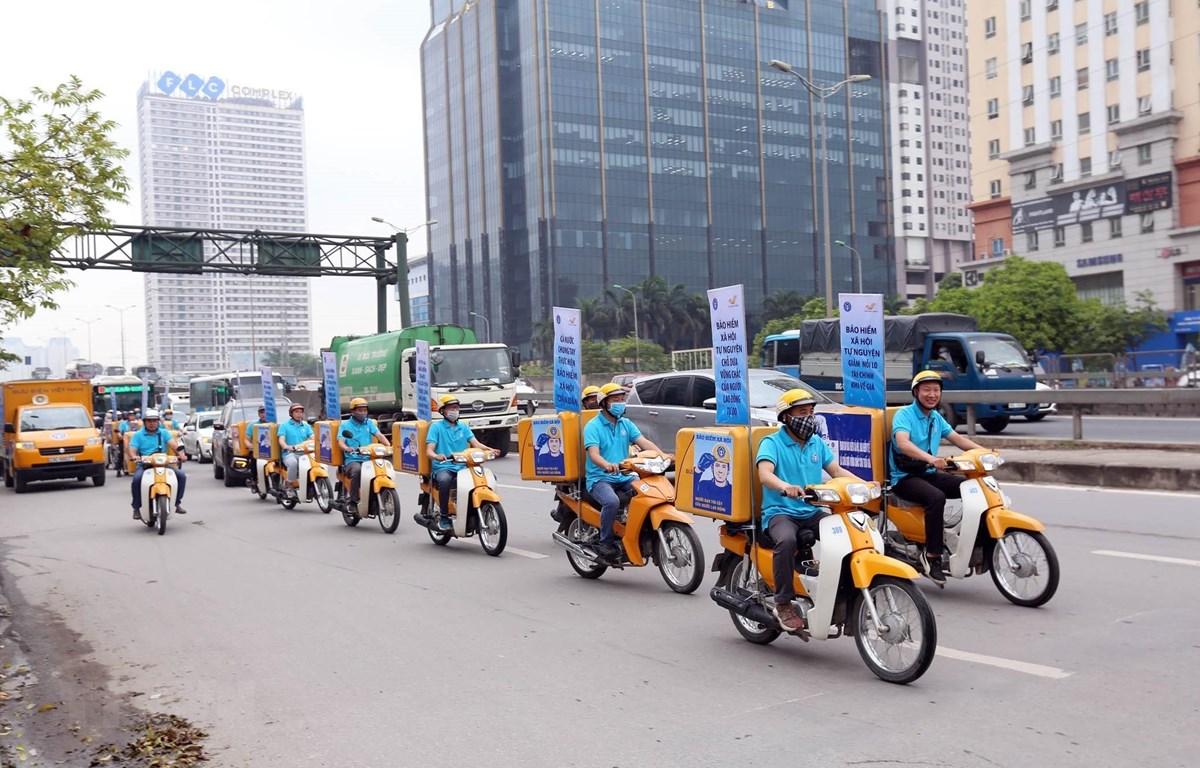 Diễu hành tuyên truyền về bảo hiểm xã hội trên các tuyến phố. (Ảnh: Anh Tuấn/TTXVN)