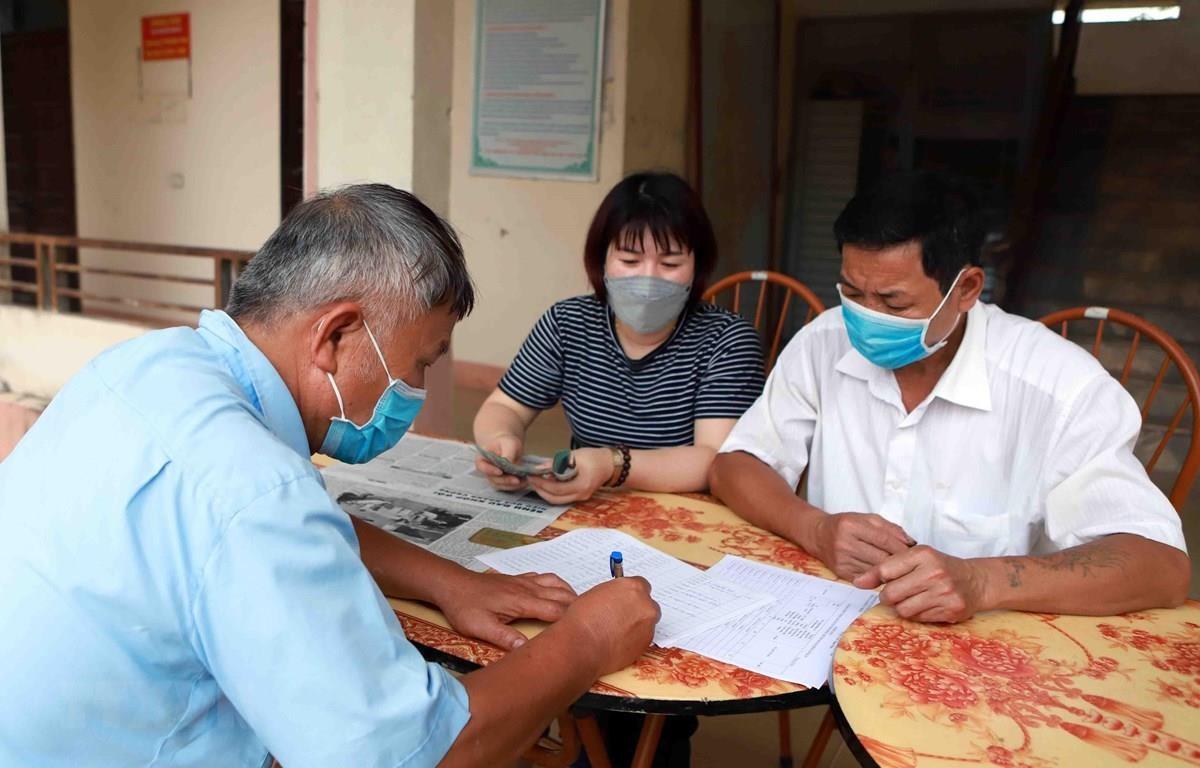 Chi trả tiền hỗ trợ cho hộ nghèo gặp khó khăn do COVID-19. (Ảnh minh hoạ: Hoàng Hùng/TTXVN)