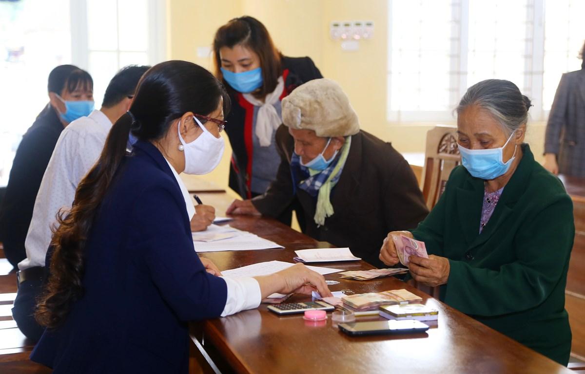 Chi trả tiền hỗ trợ cho người dân gặp khó khăn vì COVID-19. (Ảnh: PV/Vietnam+)