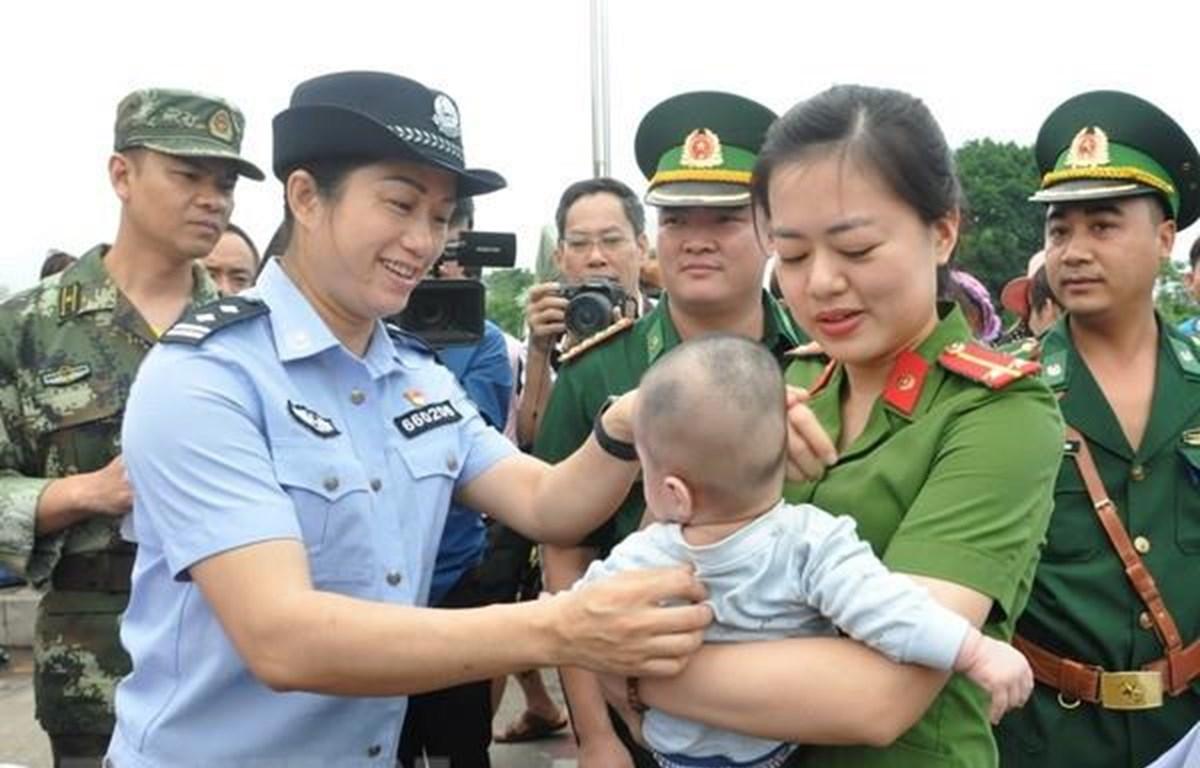 Lực lượng chức năng Việt Nam tiếp nhận em bé bị bán sang Trung Quốc. (Ảnh:Nguyễn Hoàng/TTXVN)