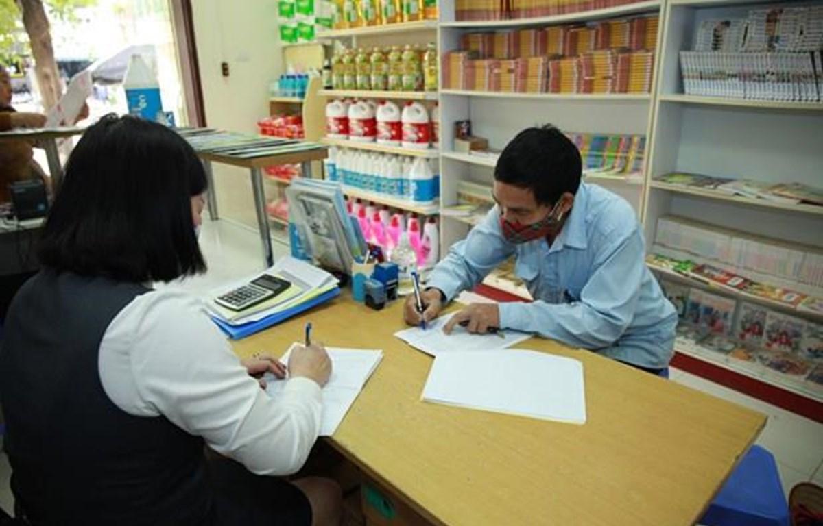 Cán bộ bưu điện chi trả trợ cấp xã hội. (Ảnh: PV/Vietnam+)