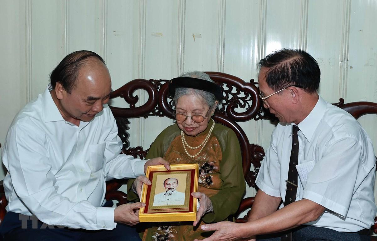 Chủ tịch nước Nguyễn Xuân Phúc đến thăm và tặng quà cho người có công. (Ảnh: Thống Nhất/TTXVN)