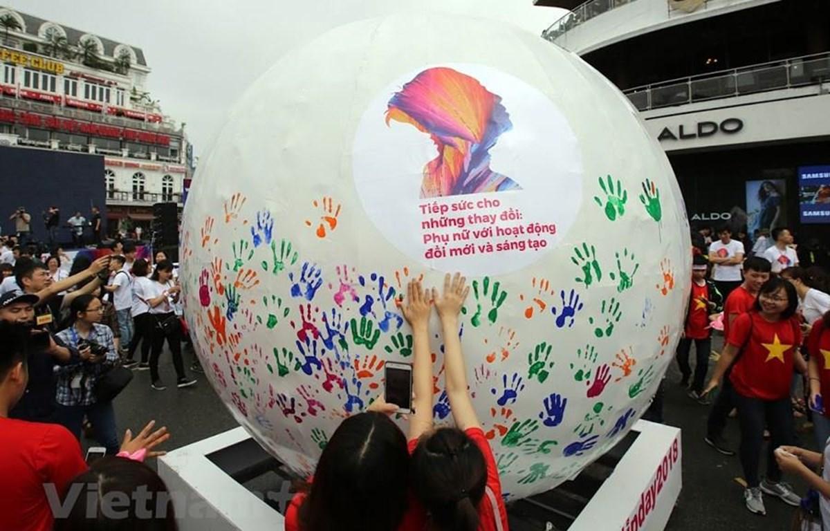 Giới trẻ in bàn tay lên Quả cầu năng lượng, tiếp thêm nguồn sức mạnh cho sở hữu trí tuệ, đổi mới sáng tạo. (Ảnh chỉ mang tính minh họa: Vietnam+)