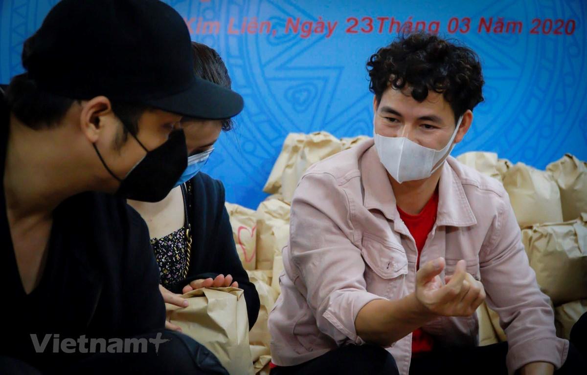 Nghệ sỹ Xuân Bắc cùng các diễn viên trẻ tham gia đóng gói những phần quà gửi tặng người khó khăn trong dịch bệnh. (Ảnh: Minh Hiếu/Vietnam+)