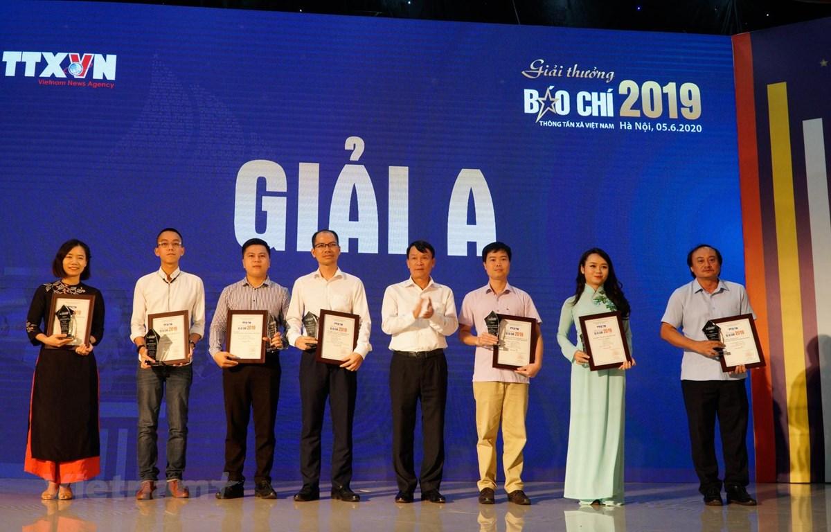 Tổng Giám đốc TTXVN Nguyễn Đức Lợi trao giải A cho các tác giả, đại diện nhóm tác giả đoạt giải. (Ảnh: Hoàng Hiếu/Vietnam+)