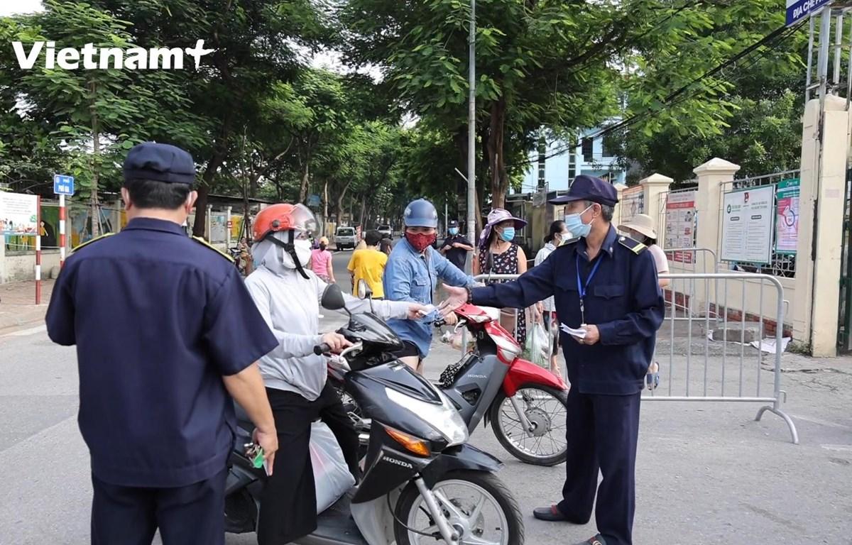 Lực lượng chức năng kiểm tra phiếu tại cổng chợ (Ảnh: Hoàng Đạt/Vietnam+)