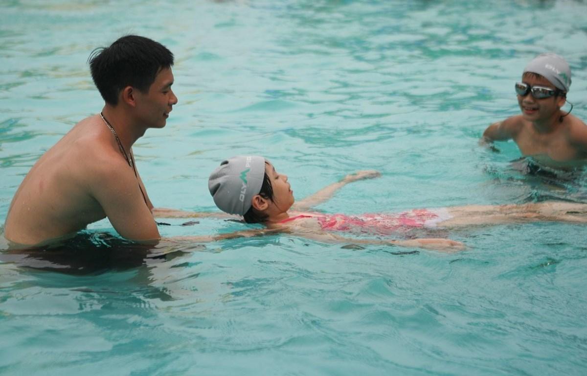 Huấn luyện viên hướng dẫn học sinh kỹ năng cơ bản để học bơi. (Ảnh: Thanh Tùng/TTXVN)