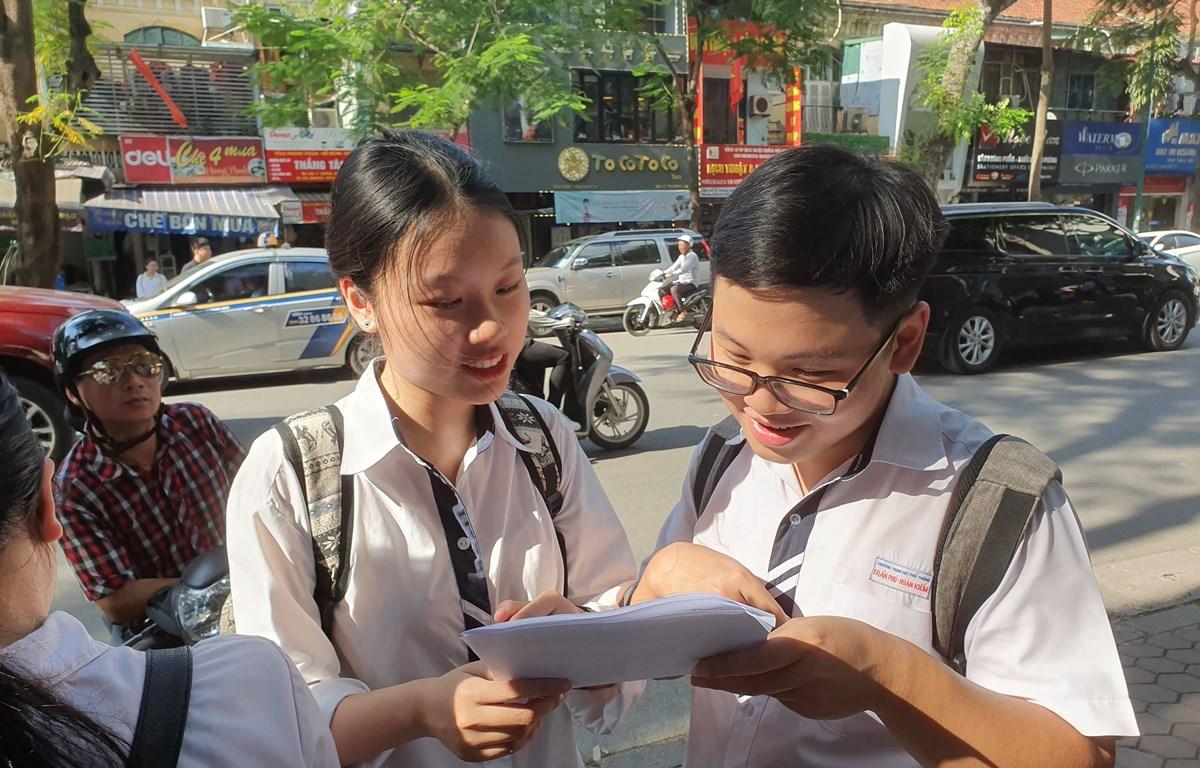 Thí sinh trao đổi bài sau buổi thi môn Ngoại ngữ. (Ảnh: Hồng Kiều/Vietnam+)
