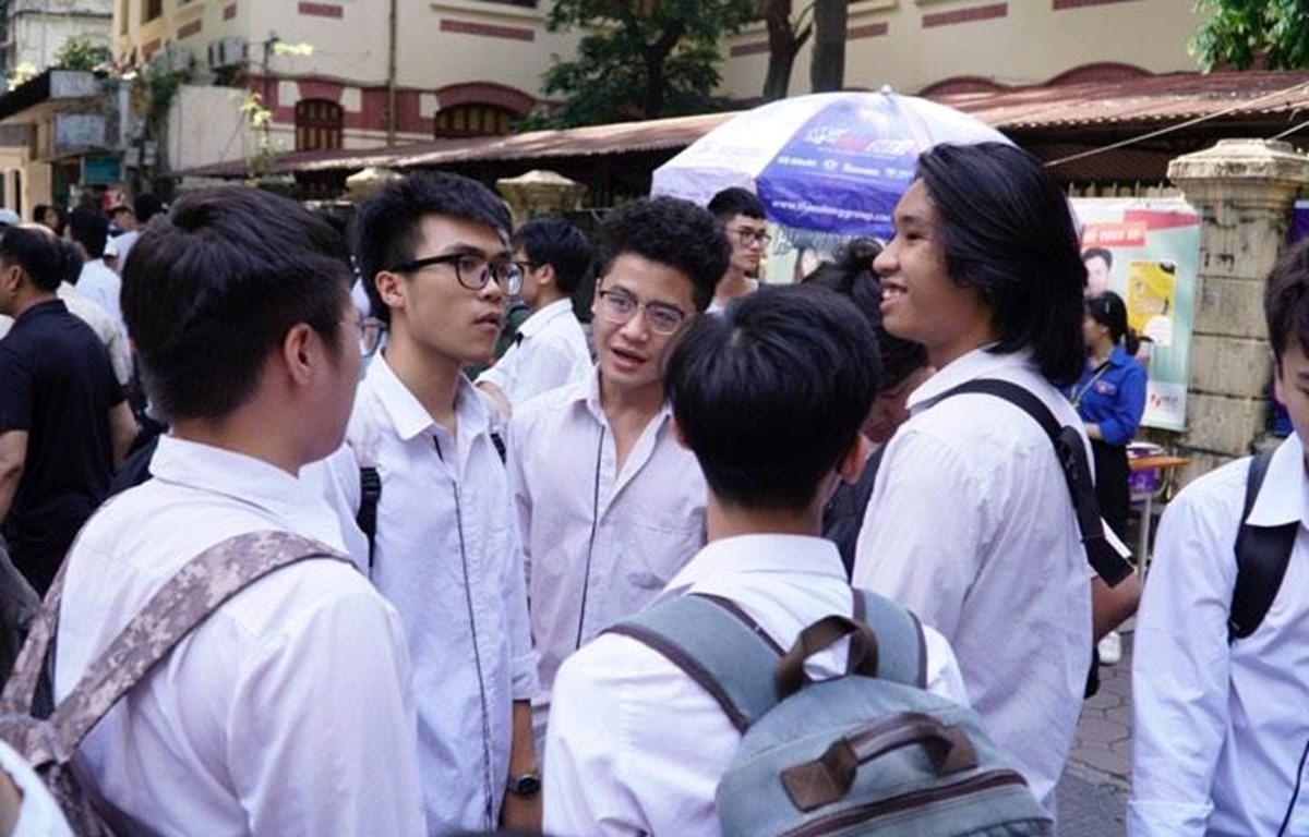 Thí sinh vui vẻ trao đổi sau khi làm xong bài thi môn Ngoại ngữ. (Ảnh: Hoàng Hiếu/Vietnam+)