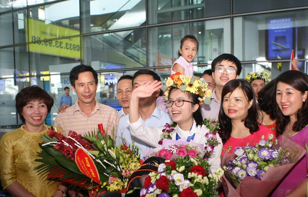Nguyễn Khánh Linh cười tươi giữa bạn bè, thầy cô và người thân đi đón tại sân bay Nội Bài. (Ảnh: Thanh Tùng)