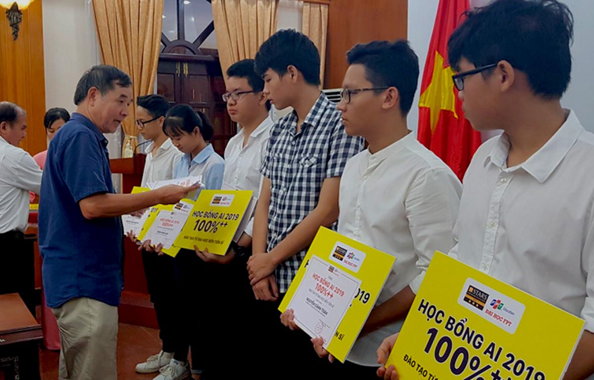 Tiến sỹ Lê Trường Tùng, Chủ tịch Hội đồng quản trị Trường Đại học FPT, trao học bổng cho các học sinh. (Ảnh: PV/Vietnam+)
