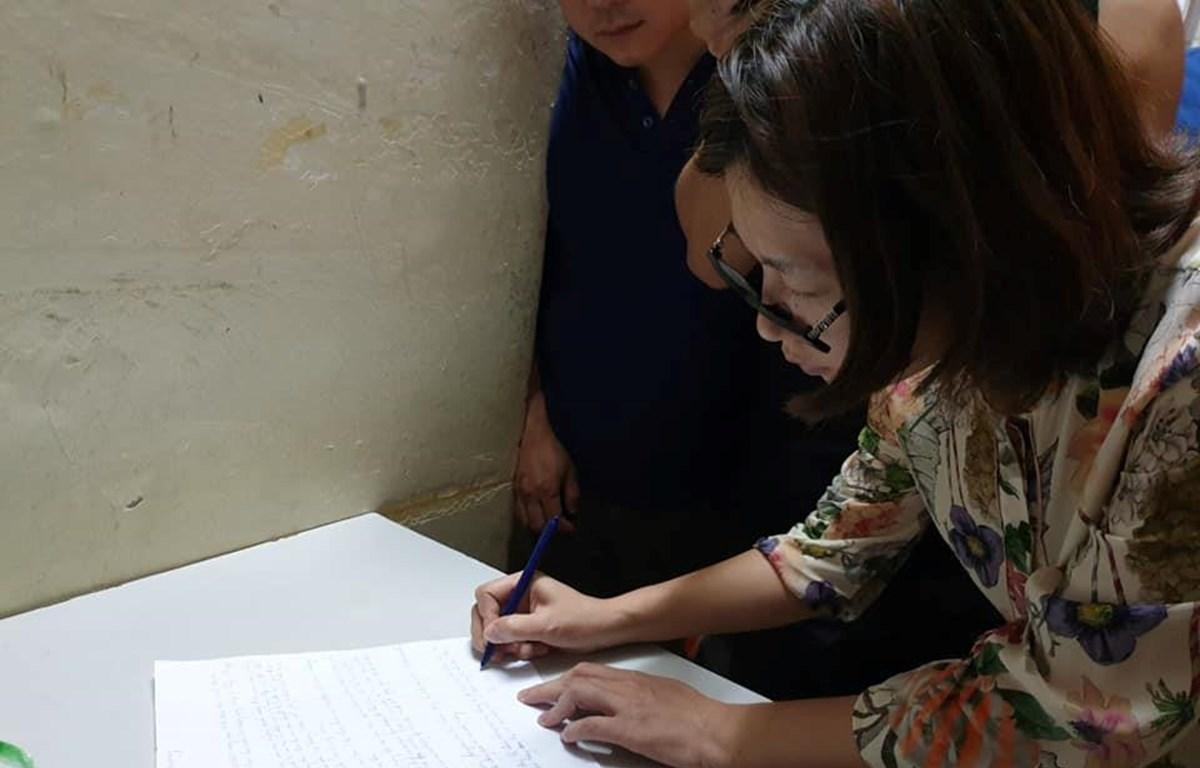 Bà Trần Thị Hồng Hạnh ký vào bản tường trình. (Ảnh: Thùy Giang/Vietnam+)