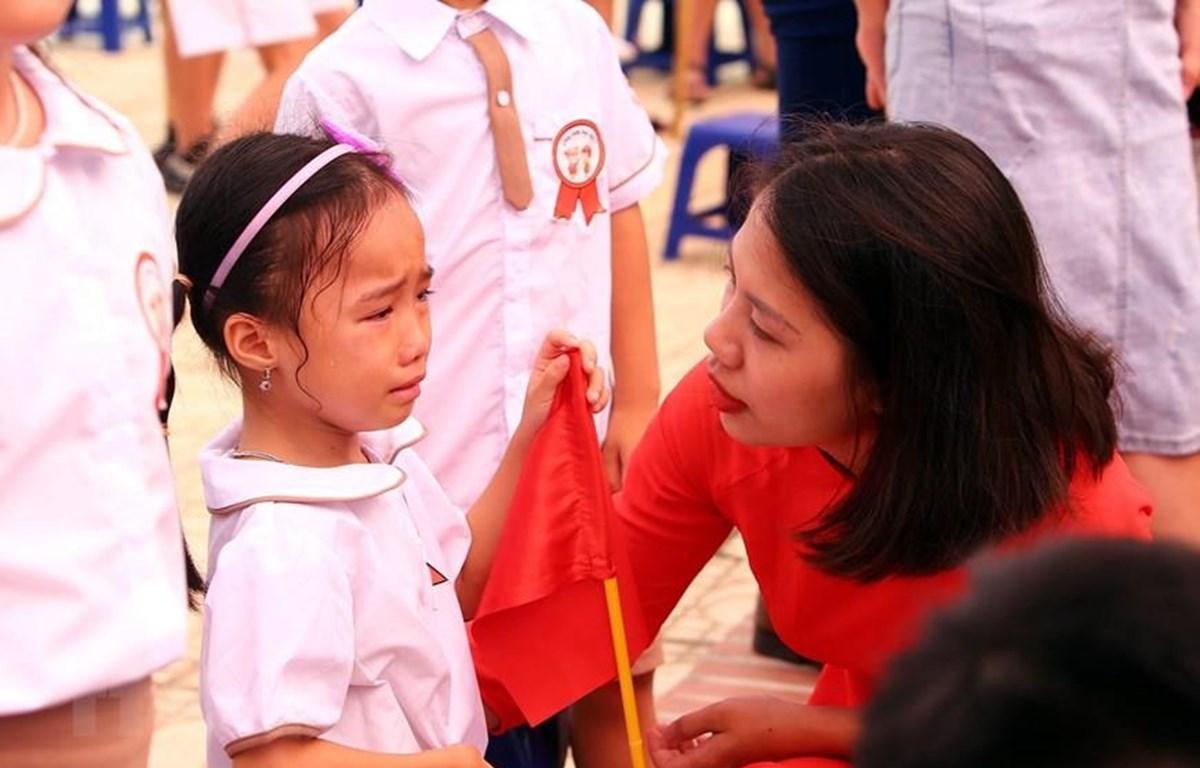 Cô giáo ân cần động viên em học sinh lớp 1 trong ngày đầu tiên đến trường tại trường Tiểu học Gia Quất, quận Long Biên (Hà Nội). (Ảnh: Danh Lam/TTXVN)