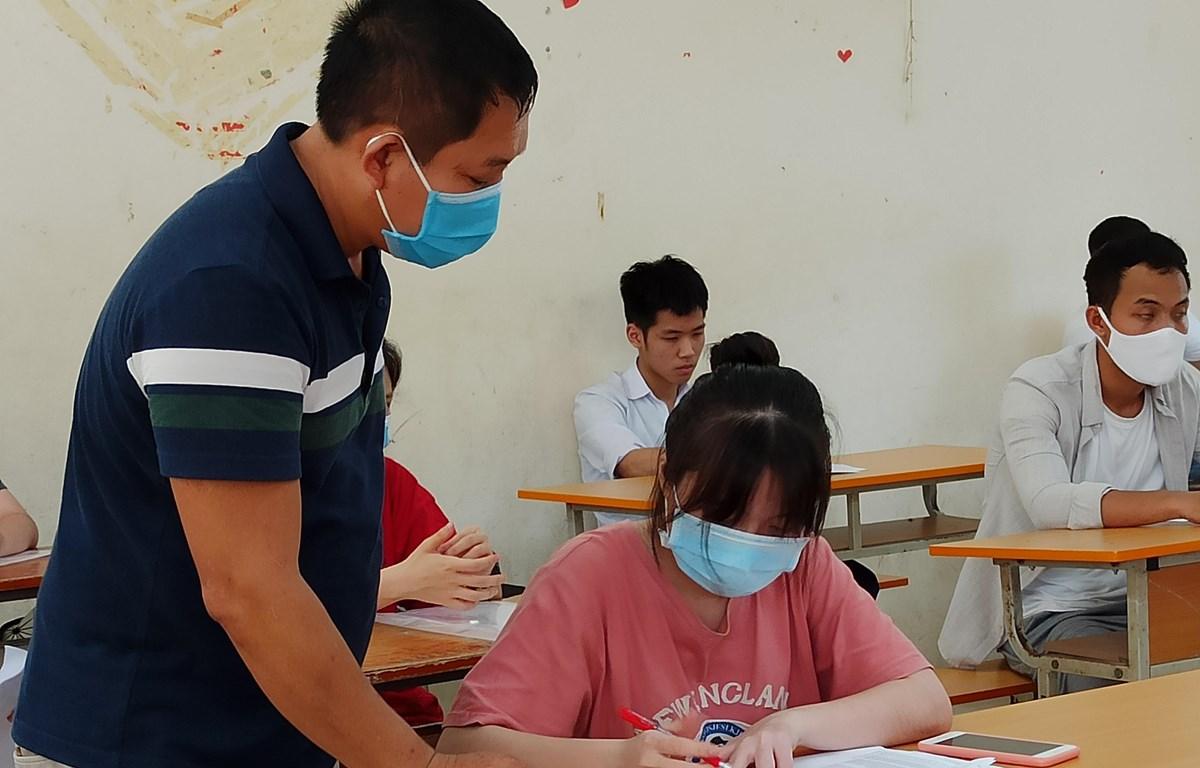 Lần đầu tiên trong lịch sử, học sinh và giám thị phải mang khẩu trang vào phòng thi vì dịch COVID-19. (Ảnh: Phạm Mai/Vietnam+)