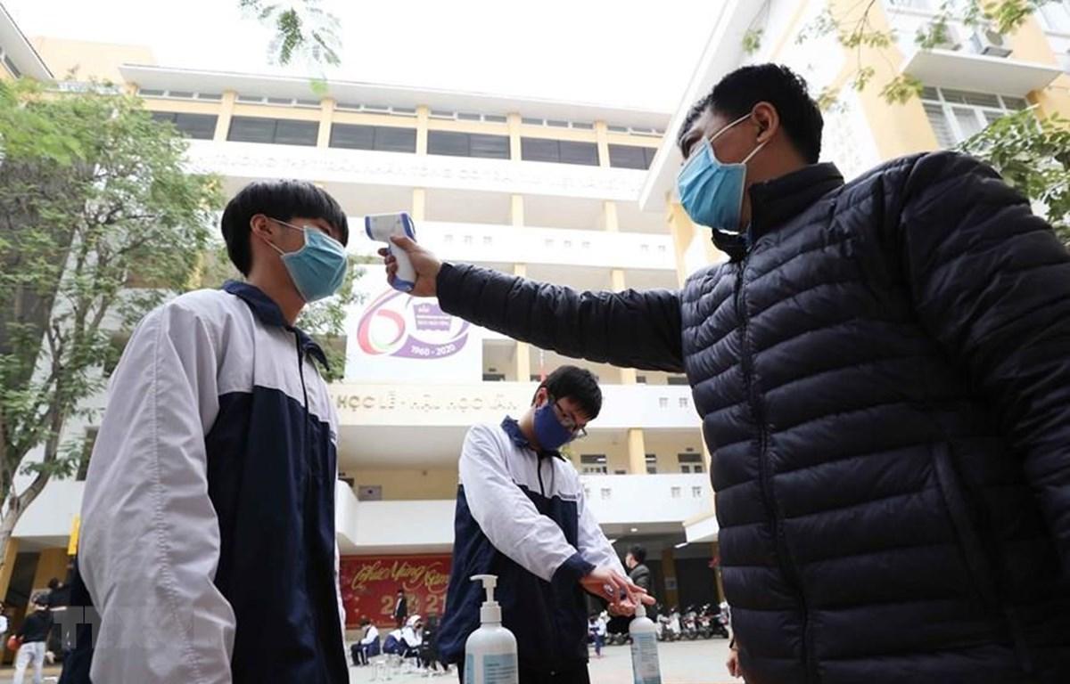 Học sinh Hà Nội được đo thân nhiệt, sát khuẩn trước khi vào trường. (Ảnh: Thành Đạt/TTXVN)