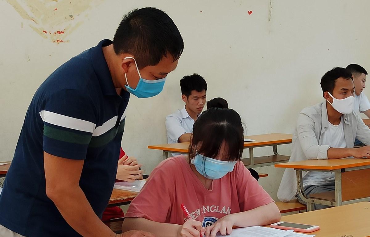 Thí sinh và giám thị cùng đeo khẩu trang vào phòng thi trong kỳ thi Tốt nghiêp Trung học phổ thông 2020. (Ảnh: Phạm Mai/Vietnam+)