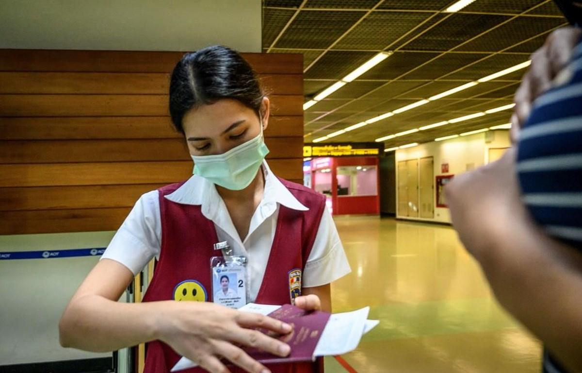 Trong ảnh: Nhân viên kiểm tra hộ chiếu của một hành khách tại sân bay Don Mueang ở Bangkok, Thái Lan ngày 21/1/2020. (Ảnh: AFP/TTXVN)