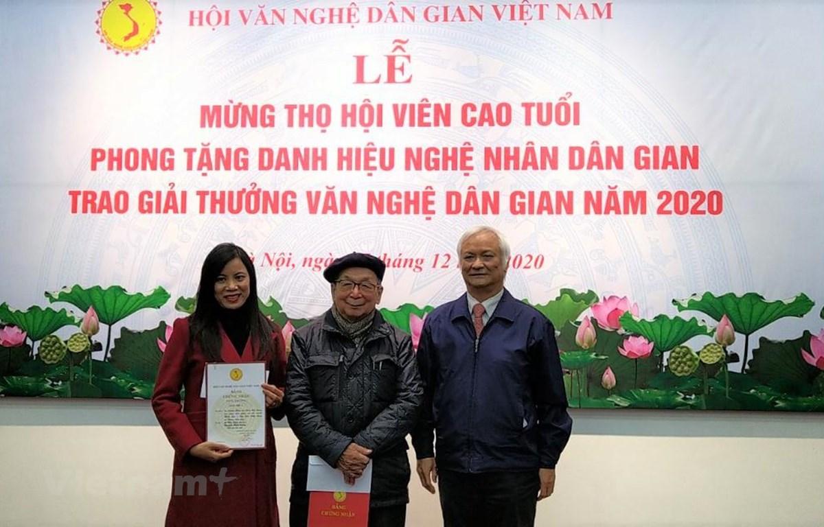 Tiến sỹ Lê Hồng Lý, Chủ tịch Hội Văn nghệ dân gian Việt Nam (phải) trao hai giải cao nhất cho các tác giả. (Ảnh: Minh Thu/Vietnam+)