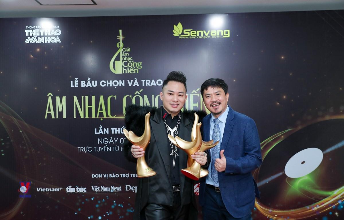 Ca sỹ Tùng Dương và nhà báo Lê Xuân Thành, trưởng ban tổ chức giải thưởng. Tùng Dương vỡ òa trong niềm vui sướng cùng 3 chiếc cúp của giải thưởng Cống hiến. (Ảnh: PV/Vietnam+)