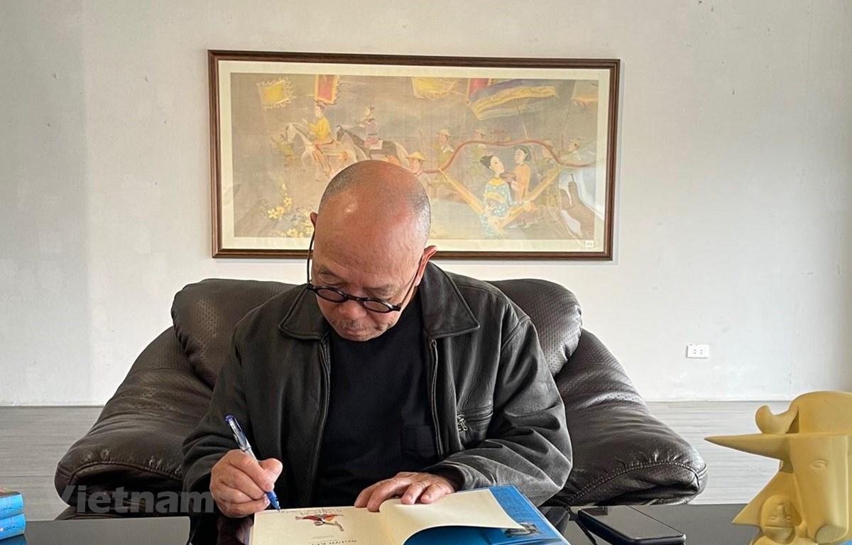Họa sỹ Thành Chương ký tên lên cuốn sách của nhà văn Kim Lân. (Ảnh: Minh Thu/Vietnam+)