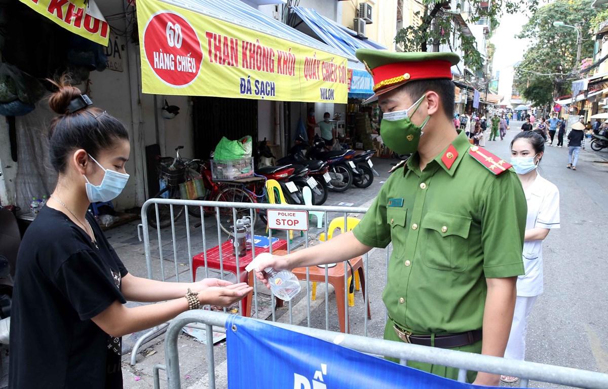 Người dân vào mua đồ thiết yếu tại chợ Đồng Xuân được lực lượng chức năng yêu cầu rửa tay sát khuẩn. (Ảnh: Phạm Kiên/TTXVN)