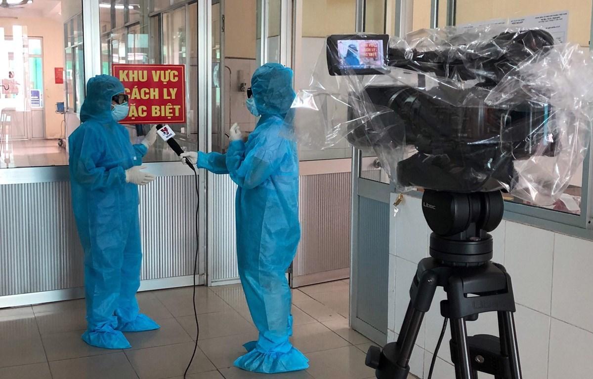 Phóng viên Thông tấn xã Việt Nam tác nghiệp trong điều kiện bảo hộ an toàn. (Ảnh: Quốc Dũng/TTXVN)