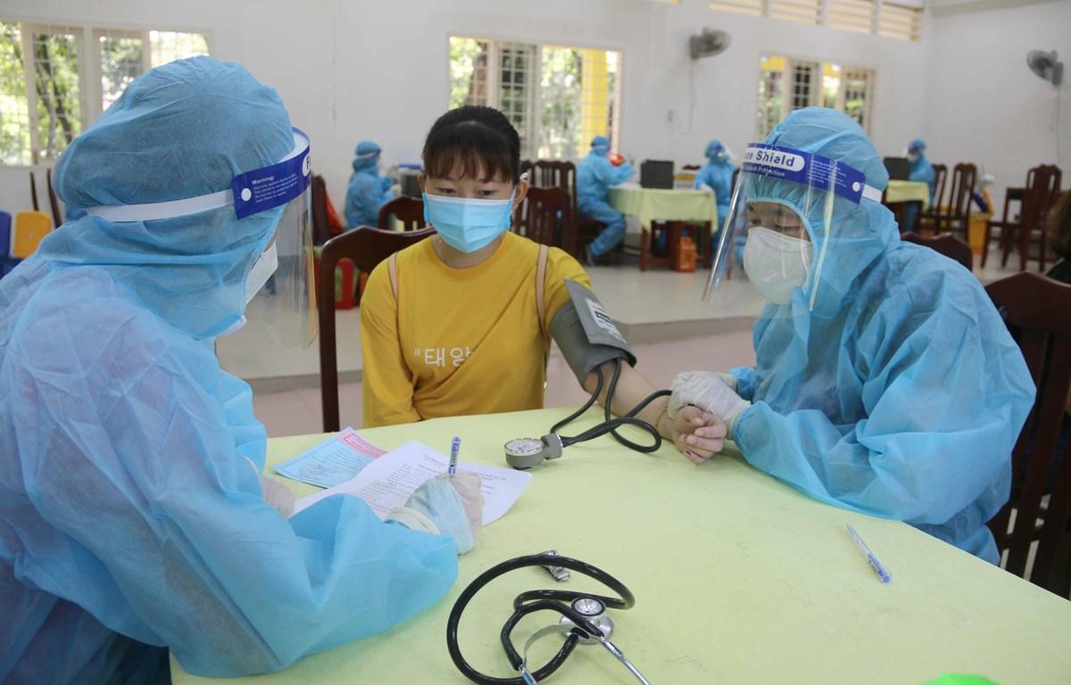 Khám sàng lọc trước khi tiêm vaccine tại điểm tiêm trường Đại học Trà Vinh. (Ảnh: Thanh Hòa/TTXVN)