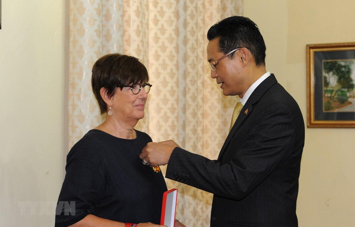 Đại sứ Việt Nam tại Cuba Nguyễn Trung Thành gắn Huân chương Hữu nghị cho bà Jehanne Roccas. (Ảnh: Vũ Lê Hà/TTXVN)