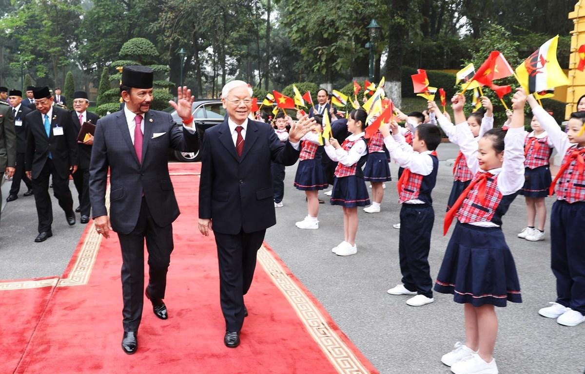 Tổng Bí thư, Chủ tịch nước Nguyễn Phú Trọng và Quốc vương Brunei Hassanal Bolkiah vẫy chào thiếu nhi Việt Nam tại lễ đón. (Ảnh: Trí Dũng/TTXVN)
