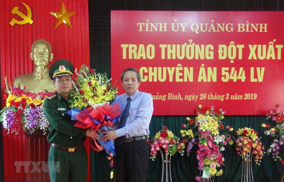 Bí thư Tỉnh ủy Quảng Bình Hoàng Đăng Quang tặng hoa cho Đại diện Bộ chỉ huy Bộ đội biên phòng Quảng Bình sau chuyên án 544LV thành công. (Ảnh: Đức Thọ/TTXVN)