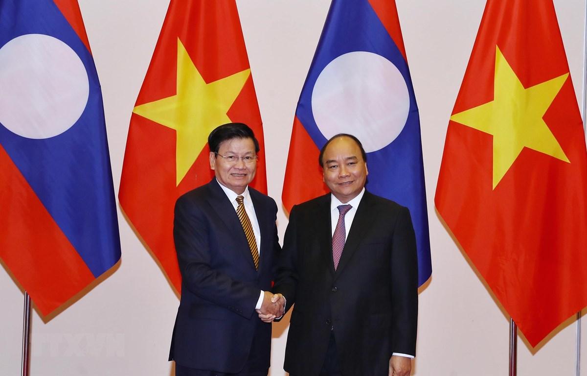 Thủ tướng Nguyễn Xuân Phúc đón Thủ tướng nước Cộng hòa Dân chủ Nhân dân Lào Thongloun Sisoulith. (Ảnh: Thống Nhất/TTXVN)