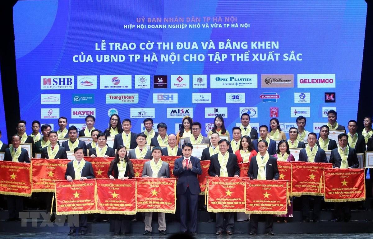 Chủ tịch Ủy ban Nhân dân thành phố Hà Nội Nguyễn Đức Chung trao bằng khen của thành phố cho các doanh nghiệp đạt thành tích xuất sắc. (Ảnh: Danh Lam/TTXVN)