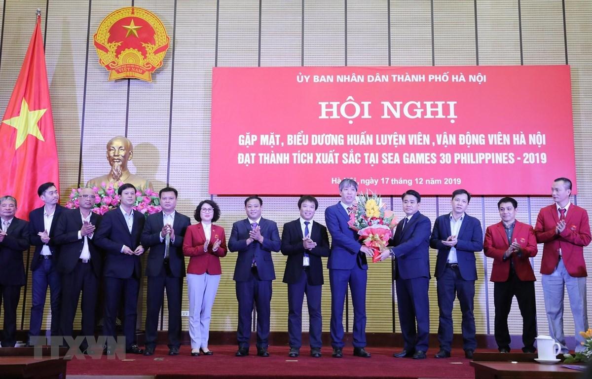 Chủ tịch Ủy ban Nhân dân thành phố Hà Nội Nguyễn Đức Chung tặng hoa, chúc mừng các bộ môn của đoàn thể thao Việt Nam. (Ảnh: Lâm Khánh/TTXVN)