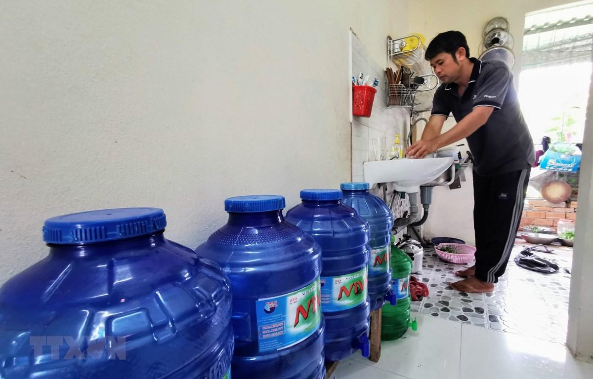 Trung bình mỗi tháng, người dân sống tại hẻm 111, đường Võ Văn Kiệt phải chi thêm khoảng 200 nghìn đồng để mua nước lọc dùng cho ăn uống. (Ảnh: Thanh Liêm/TTXVN)