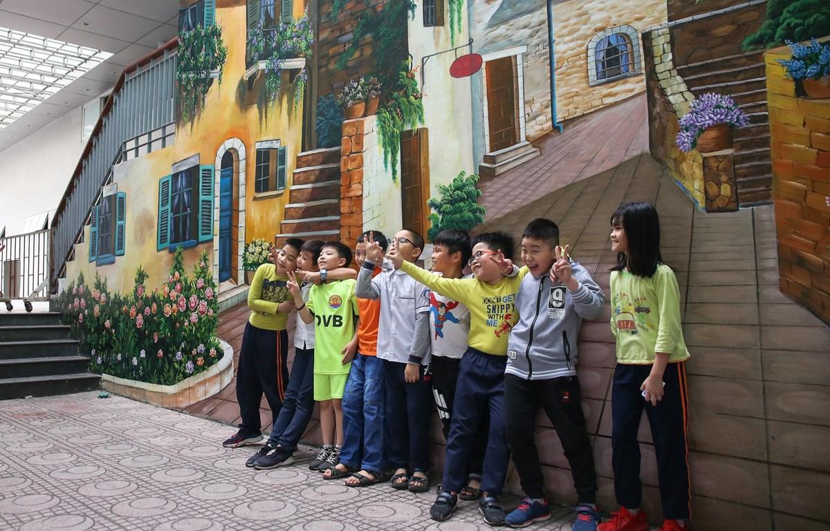 Các bạn học sinh trường Tiểu học Dịch Vọng B hồn nhiên vui đùa cùng những bức tranh tường độc đáo. (Ảnh: Quang Sỹ/Vietnam+)