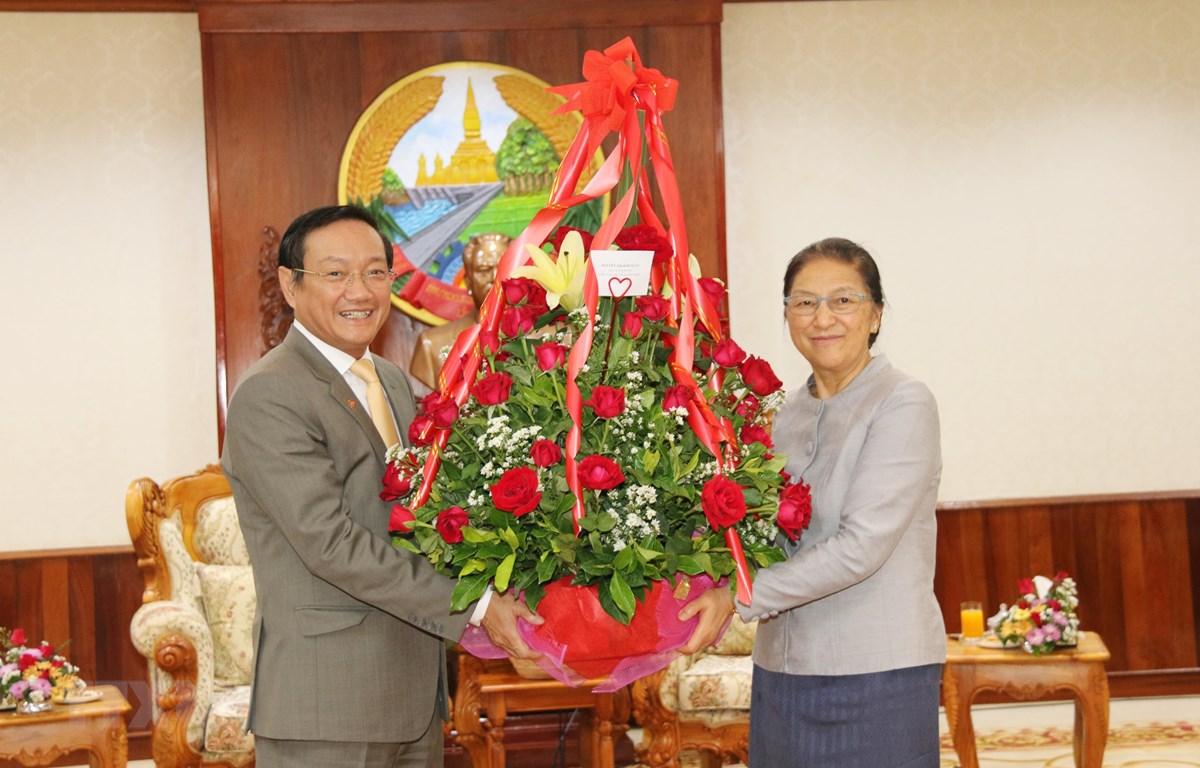 Đại sứ Nguyễn Bá Hùng (trái) chuyển hoa của Chủ tịch Quốc hội Việt Nam chúc mừng Chủ tịch Quốc hội Lào Pany Yathotou nhân dịp Bunpimay Lào. (Nguồn: Xuân Tú – Thu Phương/TTXVN)
