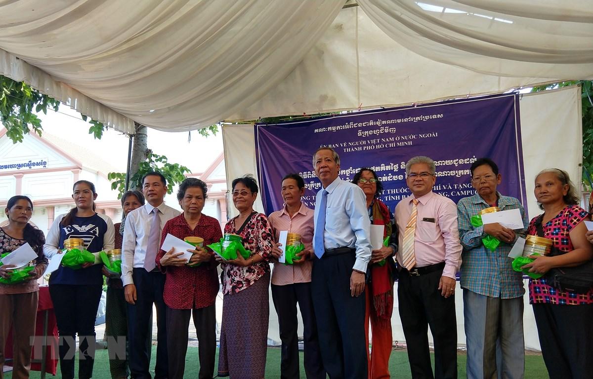 Ông Trần Đức Hiển, Phó Chủ nhiệm Ủy ban về người Việt Nam ở nước ngoài Thành phố Hồ Chí Minh cùng đại diện đoàn trao quà cho bà con. (Ảnh: Minh Hưng/TTXVN)