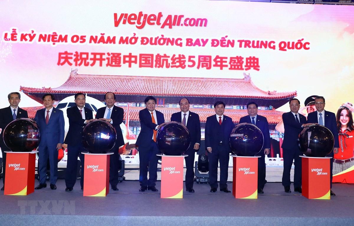 Thủ tướng Nguyễn Xuân Phúc và các đại biểu thực hiện nghi thức kỷ niệm 05 năm Vietjet Air mở đường bay tới Trung Quốc. (Ảnh: Thống Nhất/TTXVN)
